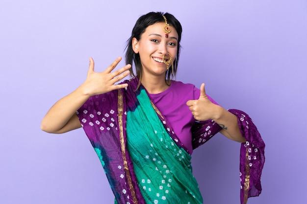 Mulher indiana isolada em roxo, contando seis com os dedos