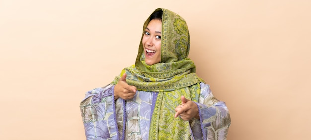 Mulher indiana isolada na parede bege, apontando para a frente e sorrindo