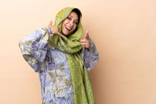 Mulher indiana isolada na parede bege, fazendo gesto de telefone e apontando a frente