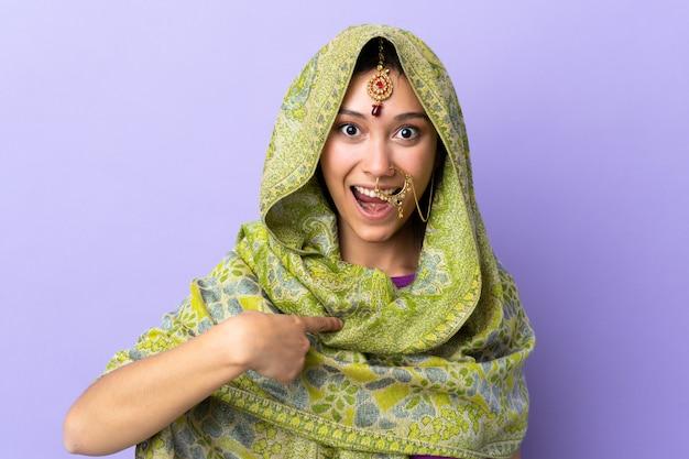 Mulher indiana isolada na parede roxa com expressão facial de surpresa