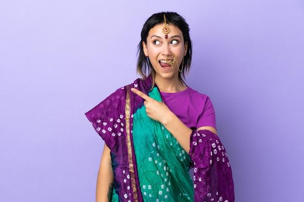 Mulher indiana isolada na parede roxa surpreendeu e apontando o lado