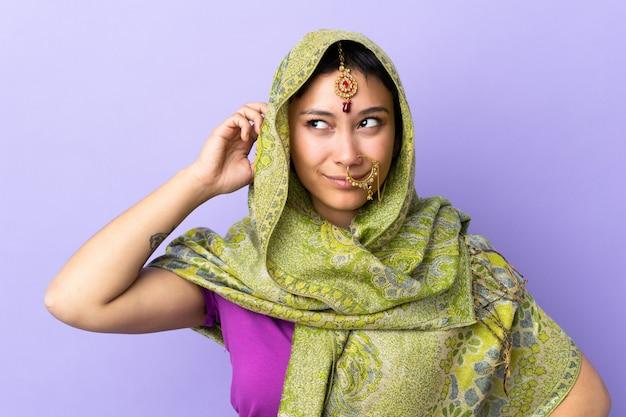 Mulher indiana isolada na parede roxa, tendo dúvidas