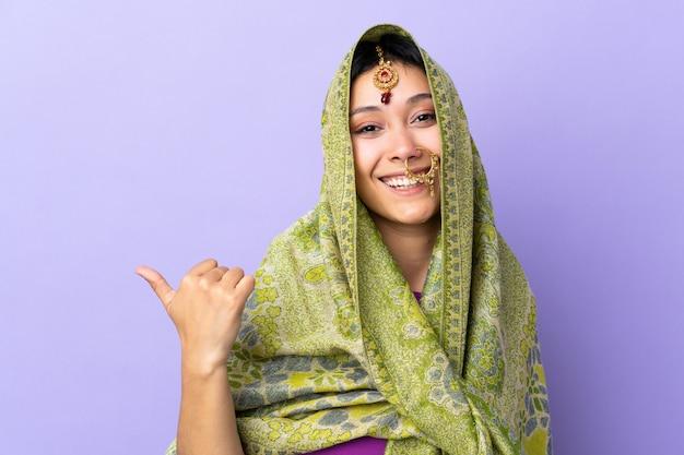 Mulher indiana isolada no fundo roxo, apontando para o lado para apresentar um produto