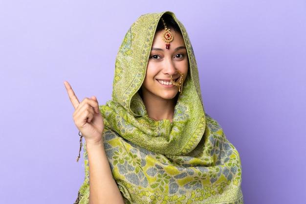 Mulher indiana isolada no fundo roxo feliz e apontando para cima