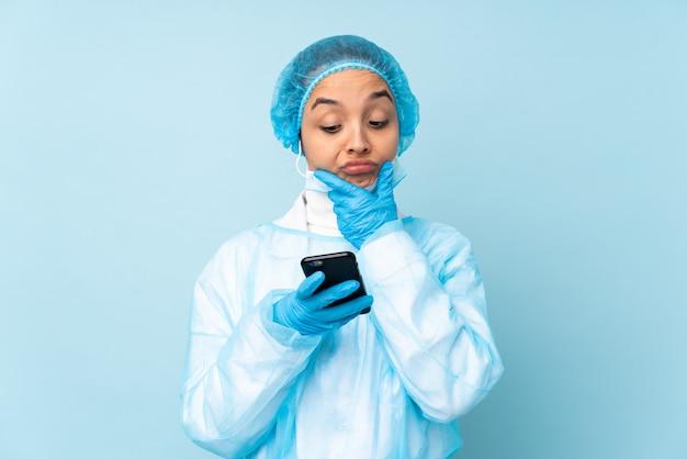 Mulher indiana jovem cirurgião em uniforme azul, pensando e enviando uma mensagem