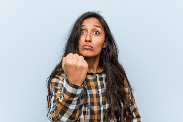 Mulher indiana legal nova que mostra o punho à câmera, expressão facial agressiva.