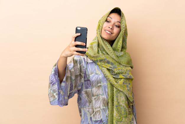 Mulher indiana na parede bege, fazendo um selfie