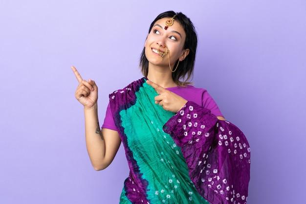 Mulher indiana na parede roxa, apontando com o dedo indicador uma ótima idéia
