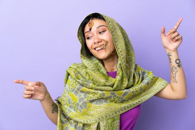 Mulher indiana na parede roxa, apontando o dedo para as laterais e feliz