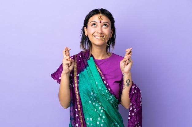 Mulher indiana na parede roxa com dedos cruzando e desejando o melhor