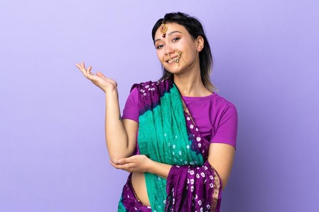 Mulher indiana na parede roxa, estendendo as mãos para o lado para convidar para vir
