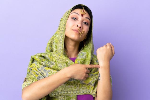 Mulher indiana na parede roxa, fazendo o gesto de chegar atrasado