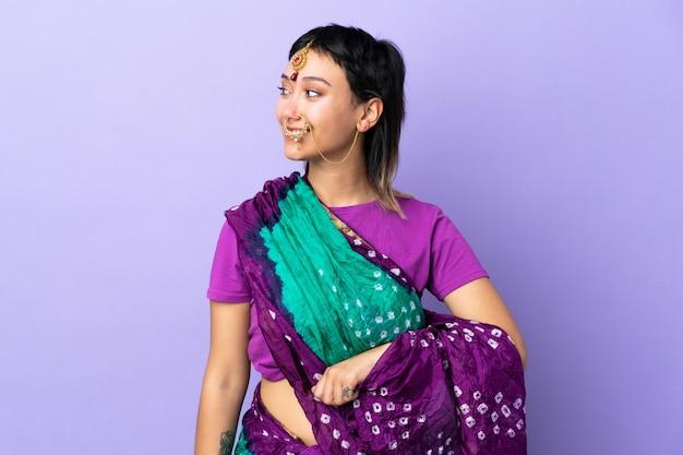 Mulher indiana na parede roxa, olhando de lado