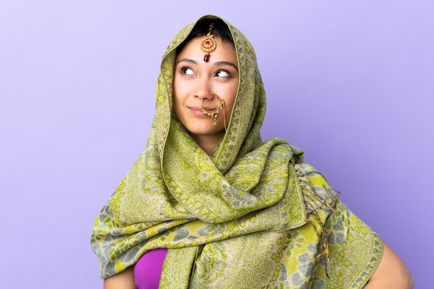Mulher indiana na parede roxa, pensando uma idéia enquanto olha para cima