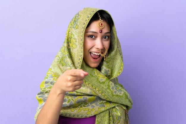 Mulher indiana na parede roxa surpreso e apontando a frente