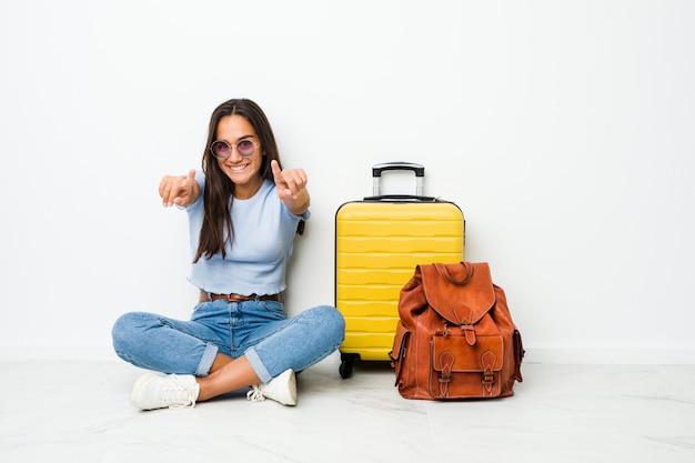 Mulher indiana nova da raça misturada pronta para ir viajar sorrisos alegres que apontam para a frente.