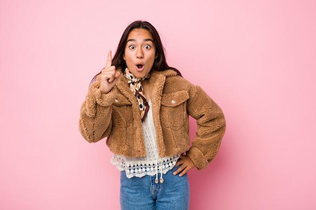 Mulher indiana nova da raça misturada que veste um casaco de pele de carneiro curto que tem uma ideia, conceito da inspiração.