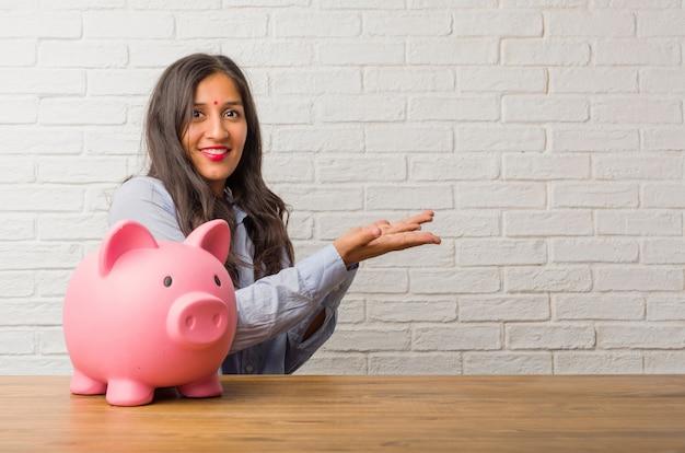 Mulher indiana nova que guarda algo com as mãos, mostrando um produto, sorrindo e alegre, oferecendo um objeto imaginário. segurando um cofrinho.