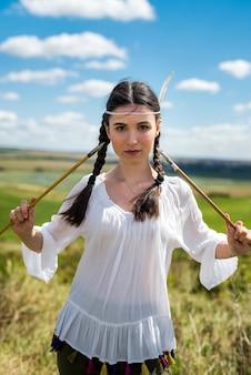 Mulher indiana posa em uma natureza circundante com flecha e arco. retrato de mulher caçadora