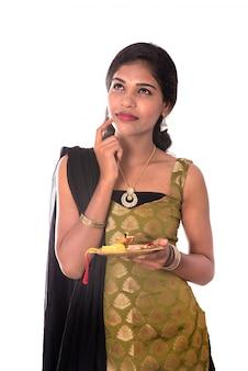 Mulher indiana que executa a adoração, retrato de uma jovem senhora bonita com o thali do pooja isolado no branco.