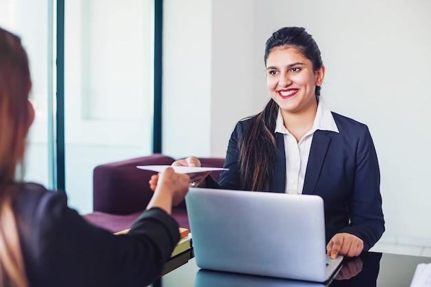 Mulher indiana que trabalha em um banco como gerente de relacionamento, emitindo aprovação de empréstimo para o cliente