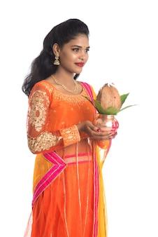 Mulher indiana segurando um kalash de cobre tradicional com coco e folha de manga com decoração floral