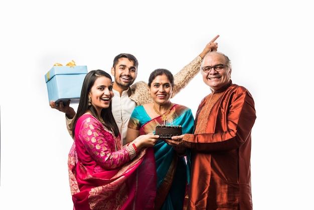 Mulher indiana sênior com família comemorando aniversário soprando velas no bolo enquanto usa roupas étnicas