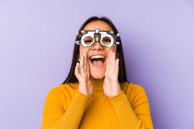 Mulher indiana youn com óculos de optometria gritando animado para a frente.
