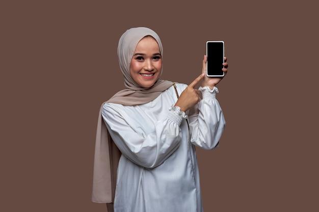 Mulher indonésia usando hijab segurando um telefone celular e apontando para a tela