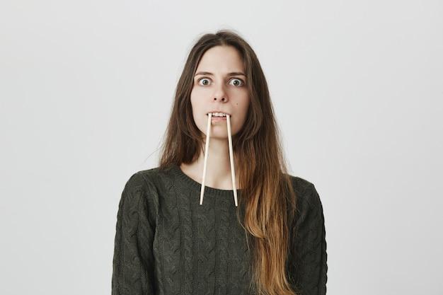Mulher infantil engraçada colocar os pauzinhos na boca, imitando presas