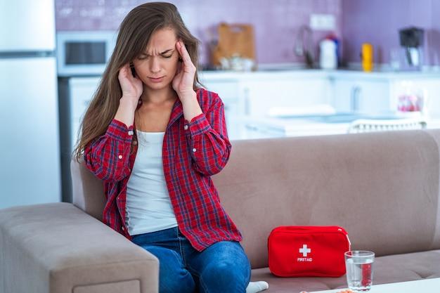 Mulher infeliz chateada doente que sofre de dor de cabeça e enxaqueca toma remédio em casa. kit de primeiros socorros médicos com pílulas e analgésicos de doenças e dores