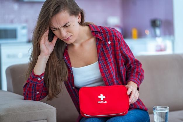 Mulher infeliz chateada doente que sofre de forte dor de cabeça e enxaqueca toma remédio em casa. kit de primeiros socorros médicos com pílulas e analgésicos de doenças e dores