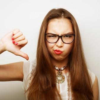 Mulher infeliz dando polegares para baixo gesto olhando com expressão negativa e desaprovação.