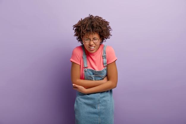 Mulher infeliz de cabelo encaracolado cruzando os braços sobre a barriga