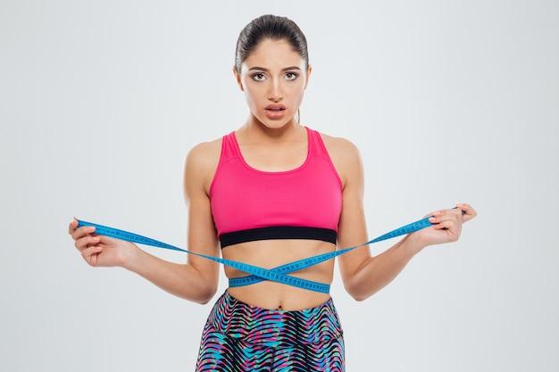 Mulher infeliz de esportes medindo a cintura com fita adesiva