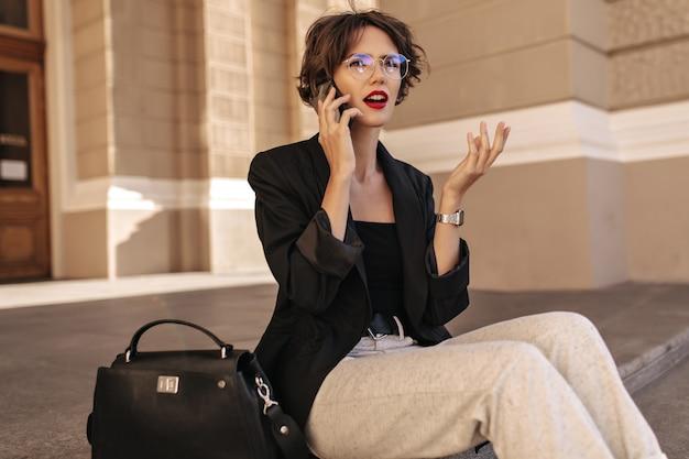 Mulher infeliz de jaqueta preta e óculos fala no telefone do lado de fora. mulher moderna, com lábios vermelhos e cabelo encaracolado, senta-se ao ar livre.