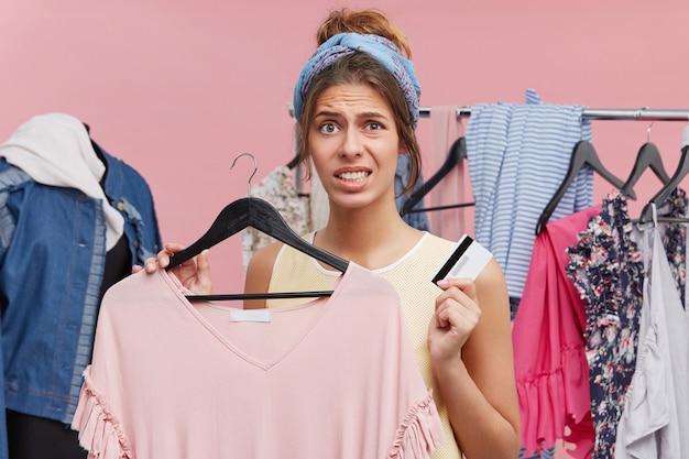 Mulher infeliz fazendo compras, em pé na loja de roupas, segurando o vestido novo e cartão de crédito, sendo tiro de dinheiro, tendo crise financeira, querendo comprar roupas novas imediatamente. compras