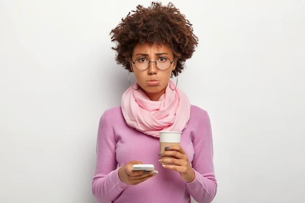 Mulher infeliz franze o lábio inferior, sente-se abatida porque o namorado não liga a tempo, segura o celular para o encontro, bebe café para viagem