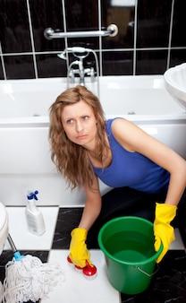 Mulher infeliz que limpa o chão do banheiro