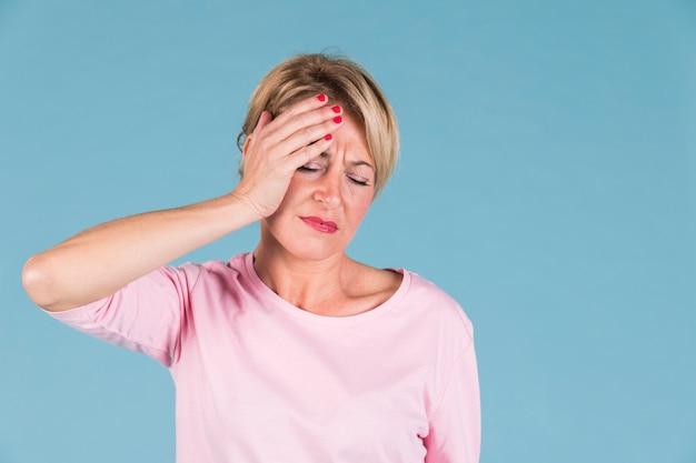 Mulher infeliz que sofre de dor de cabeça contra o fundo colorido