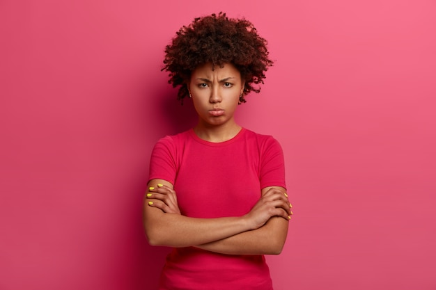 Mulher infeliz ressentida parece com uma careta carrancuda, cruza os braços sobre o corpo, descontente com o mau tratamento, parece zangada, usa uma camiseta vermelha, posa sobre a parede rosa. emoções negativas
