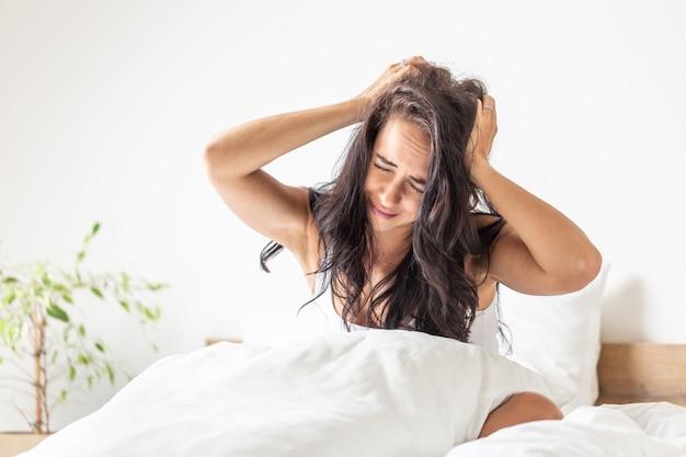 Mulher infeliz segura a cabeça ao acordar após dormir pouco na cama.