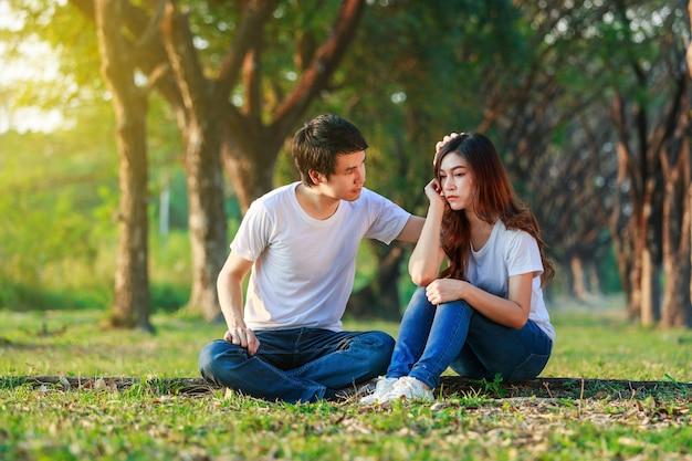 Mulher infeliz sentado com um cara preocupado, consolando-a no parque