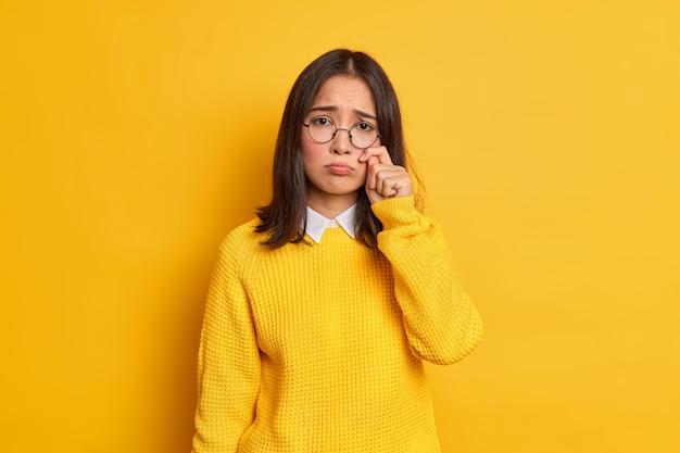 Mulher infeliz, triste e abatida com aparência oriental, esfrega lágrimas, quer chorar, sente-se desesperada, tem problemas na vida, usa óculos redondos e suéter casual.