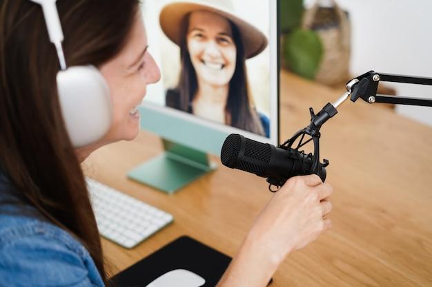 Mulher influenciadora fazendo podcast usando o computador em casa - conceito de tendência de tecnologia - foco no microfone