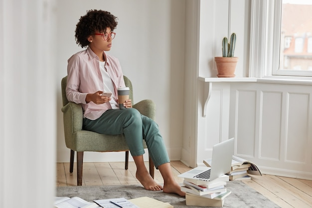 Mulher iniciante bem-sucedida e bem-sucedida gosta de bebida cappuccino, segura o copo para viagem, senta-se na poltrona, usa o telefone celular e o laptop