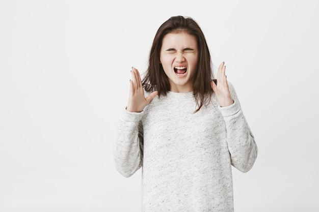 Mulher insatisfeita e louca, que grita com os olhos fechados e gesticula, expressando raiva.