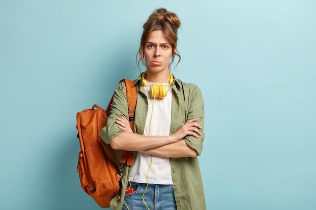 Mulher insatisfeita mantém os braços cruzados, olha furiosa para a câmera, não quer ter aula, carrega mochila