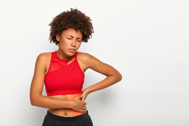 Mulher insatisfeita segura o quadril dolorido, tem inflamação nos rins, toca o local da dor perto das costelas marcado com um ponto vermelho, usa sutiã esportivo