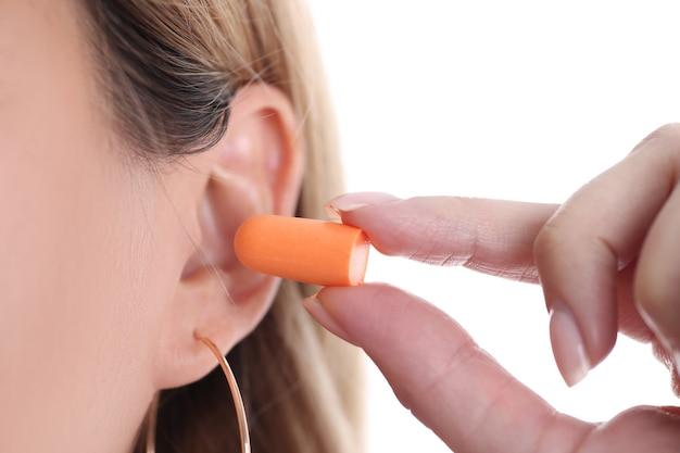 Mulher insere tampões de ouvido laranja suave na orelha, close-up
